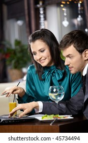 Young woman and the man discuss something on the laptop screen in cafe