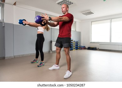 Young Woman And Man Doing Exercise With Kettle Bell In The Gym