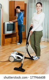 Young  woman and man doing housework together in home