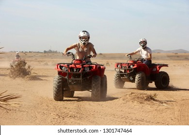 Young woman and man driving Quadbikes in desert area outside of Marrakech, Morocco