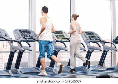 Young woman and man at the gym exercising. Run on a machine.