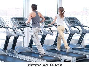 Young woman and man at the gym exercising. Run on on a machine.