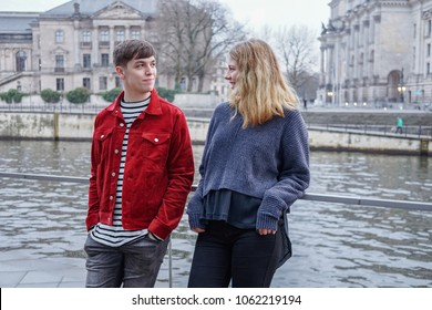 young woman and man hanging out by the river Spree in Berlin, Germany, with Bundestag Reichstag building in the background