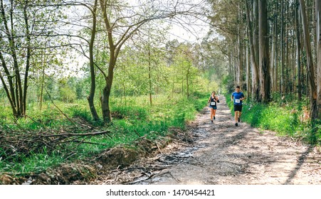 Young woman and man participating in a trail race through the forest