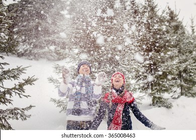 Young woman and man playing with snow.