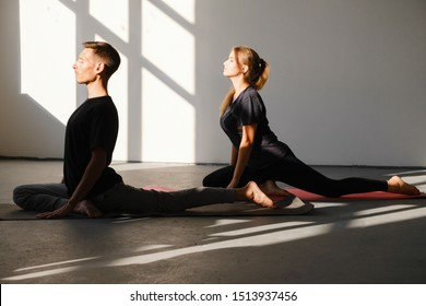 Young woman and man practicing yoga, doing Single Pigeon, Eka Pada Raja Kapotasana exercise, One Legged King Pigeon pose, working out, wearing sportswear, yoga studio