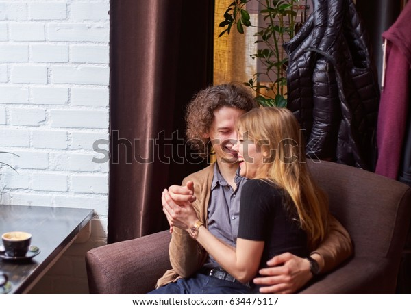 A young woman and man sit embraced and laughing