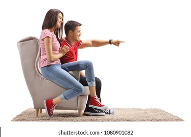 Young woman and a young man sitting in an armchair with the young man pointing isolated on white background
