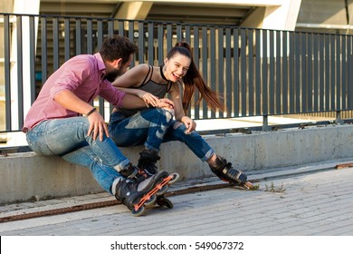 Young woman and man sitting. Lady on rollerblades laughing. Laugh until your belly hurts.