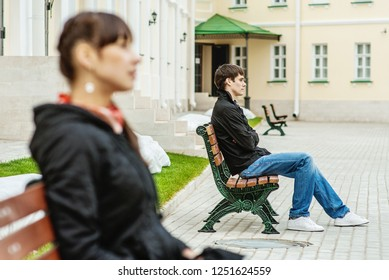 A young woman and a young man sitting on different benches around the beautiful buildings.