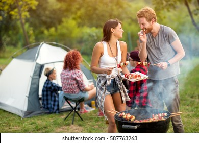 Young woman and man smiles while man tasting roasted barbecue in campground