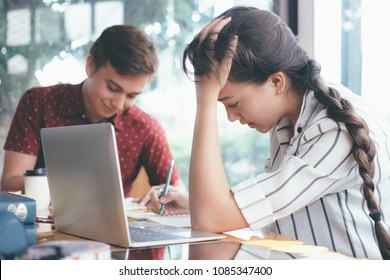 Young woman and man studying for a test or an exam. Tutor books with friends. Young students campus helps friend catching up and learning. People, learning, education and school concept.