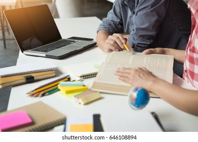 Young woman and man studying for a test/ an exam. Tutor books with friends. Young students campus helps friend catching up and learning. People, learning, education and school concept