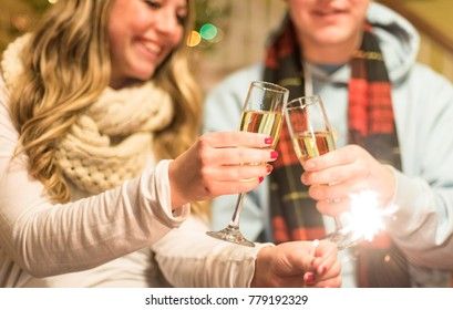 Young woman and young man toasting with champagne glasses in winter