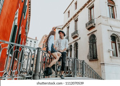 Young woman and man in Venice. couple in love in Italy on a background of vintage old building. Romantic tourists celebrate summer vacation.