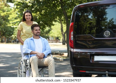 Young woman with man in wheelchair near van outdoors