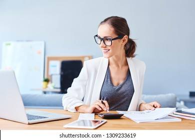 Young woman managing budget using calculator in office and smiling