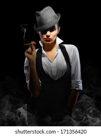 Young woman in manly style with cigar on smoky background