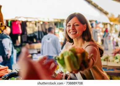 Young woman at the market choosing vegetables.