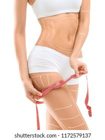 Young woman with marks for liposuction operation and measuring tape on white background. Cosmetic surgery