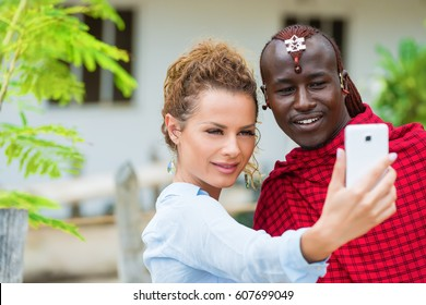 Young woman and Masai man taking self portrait photo, selfie outdoors