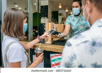 Young woman with mask paying with mobile a take away order