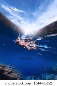 A young woman in a mask for snorkeling and in flippers dives into the Red Sea to look at the coral and colorful fish