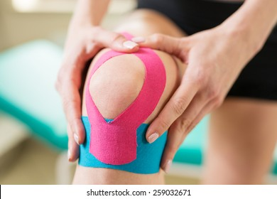Young woman massage injured knee with kinesiotaping