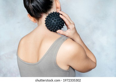 Young woman massages her back with spiky trigger point ball, muscle pain treatment reflexology. Physiotherapy concept