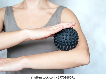 A young woman massages her elbow with spiky trigger point ball, tennis elbow exercises