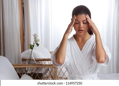 Young woman massaging her face wearing bathrobe.