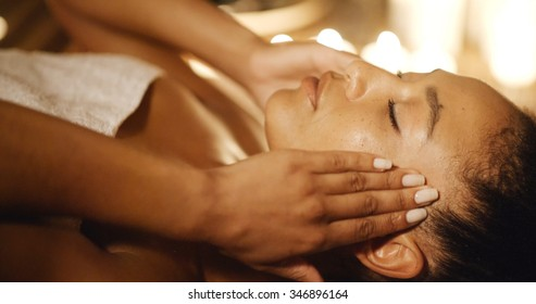 Young woman massaging her face while lying on a massage table in the spa salon
