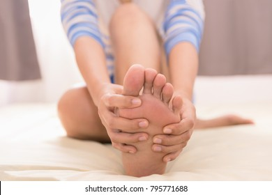 Young woman massaging her foot on the bed., Healthcare concept
