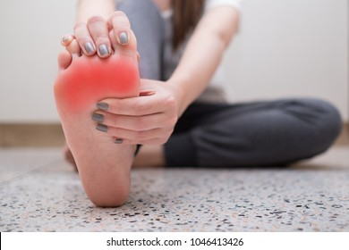 Young woman massaging her pain foot. Health care concept