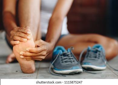 Young woman massaging her painful foot from exercising and running