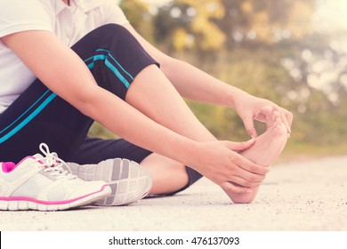 Young woman massaging her painful foot from exercising and running, Vintage style.