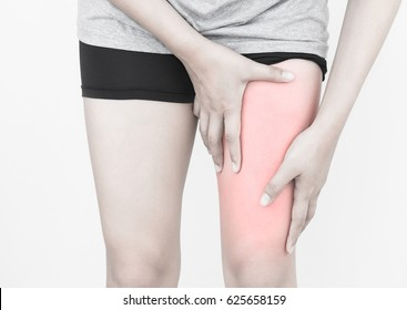 Young woman massaging her painful thigh muscles from exercising and running.