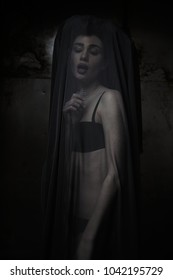 young woman in matching black lingerie veiled by sheer black fabric prying