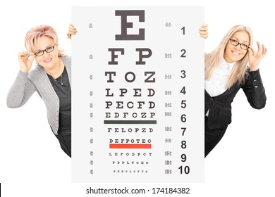 Young woman and a mature lady with glasses standing behind eyesight test isolated on white background