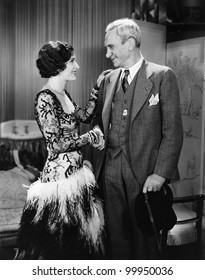 Young woman and mature man shaking hands