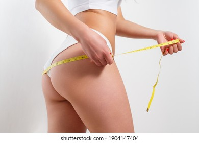 A young woman measures the volume of her thighs with a centimeter tape. On a white background.