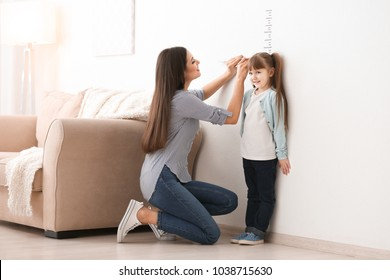 Young woman measuring her daughter's height indoors