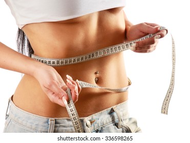 A young woman measuring her waist, focus on her belly