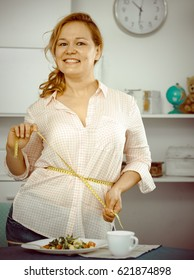 Young woman measuring her waist with measuring tape to control volume and weight at vegetable diet