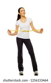 Young woman measuring her waistline with a measuring tape over white background.