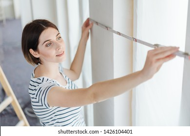 Young woman measuring the width of a window with newly painted white walls while redecorating her house