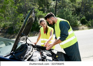 young woman and mechanic assistance on roadside with car breakdown