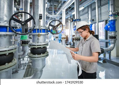 Young woman mechanical engineer holding drawing to checking and inspection of HVAC heating ventilation air conditioning system on pressure gauge of industrial air compressor boiler pump room system