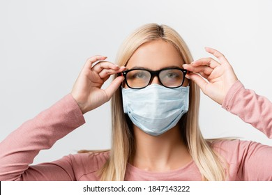 Young woman in medical mask holding misted eyeglasses isolated on grey