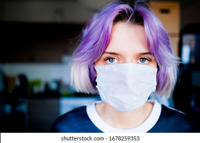 Young woman in a medical mask looks to the camera inside her house.